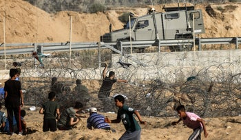 A Palestinian protester hurls rocks at an Israeli army vehicle during clashes between Palestinian protesters and Israeli forces across the barbed-wire fence in the southern Gaza Strip on July 19, 2019