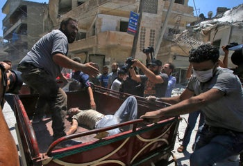 Syrian men load the body of a victim into a truck at the site of a reported air strike on the town of Ariha, in the south of Syria's Idlib province on July 27, 2019