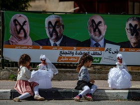 Children play in front of a vandalized Balad campaign poster in Kfar Reina, April 8, 2019.