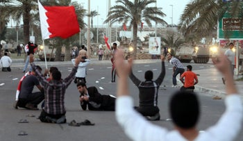 Bahraini protesters sit down in front of army tanks February 18, 2011.