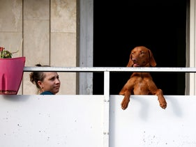 A woman sits on a balcony with her dog during the annual gay pride parade in Jerusalem June 6, 2019