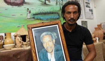 Naftali Aklum holding a framed photograph of his brother Farede Yazazao Aklum, who helped coordinate the rescue of thousands of Ethiopian Jews during Operation Brothers in the 1980s.