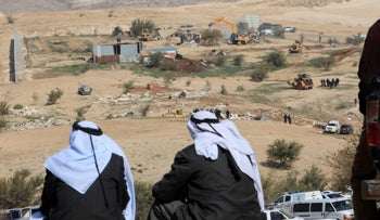 Two Bedouin men watch their houses being demolished in the village of Umm al-Hiran, in 2017.
