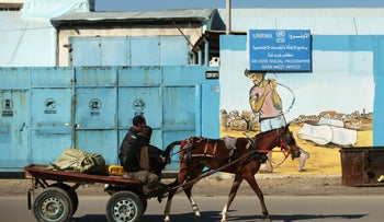 A Palestinian man rides his horse past the UNRWA relief and social program office in Gaza City, January 8, 2018.