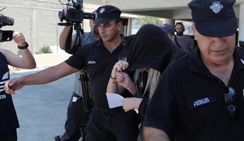 Elite police unit officers escort a 19-year old British woman, center with head covered, to Famagusta court in Paralimni, Cyprus, Tuesday, July 30, 2019.
