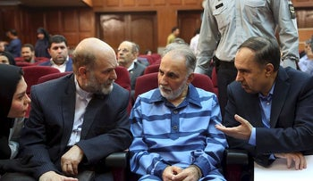 Former Tehran mayor Mohammad Ali Najafi (2nd-R), accused of shooting his second wife, speaks with his lawyer ahead of his trial at Iran's criminal court on July 13, 2019.