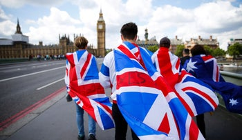 People walk over Westminster Bridge wrapped in Union flags, towards the Big Ben and The Houses of Parliament in central London on June 26, 2016.