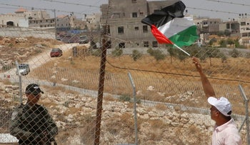 A Palestinian protester waves the national flag at an Israeli border guard at a protest against Israel's demolition of buildings in the East Jerusalem neighborhood of Sur Baher (in background). July 26, 2019
