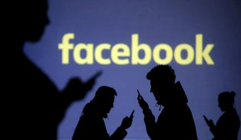 An illustration of mobile users next to a screen projection of the Facebook logo, March 28, 2018.