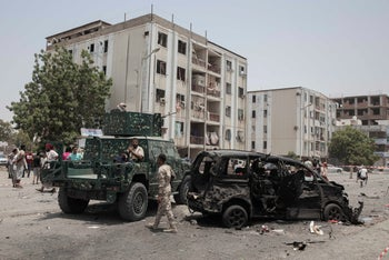 Civilians and security forces gather at the site of a deadly attack on the Sheikh Othman police station, in Aden, Yemen, Thursday, Aug. 1, 2019.