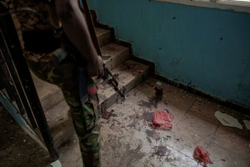 A solider walks past blood after a deadly attack on the Sheikh Othman police station in Aden, Yemen, Thursday, Aug. 1, 2019.
