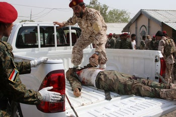 A soldier moves a dead body to a truck after a missile attack on a military parade during a graduation ceremony for newly recruited troopers in Aden, Yemen August 1, 2019.