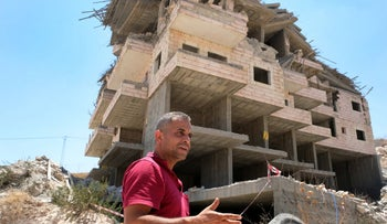 Muhammad Abu Tair in front of his demolished apartment building.