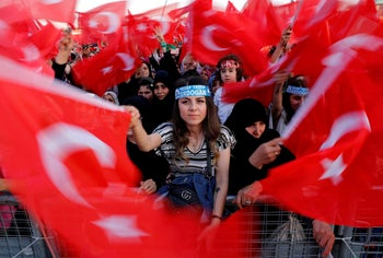 Supporters of Turkish President Tayyip Erdogan wave national flags during a ceremony marking the third anniversary of the attempted coup at Ataturk Airport in Istanbul, Turkey, July 15, 2019