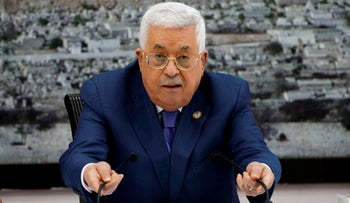 Palestinian President Mahmoud Abbas fixes the microphones during a meeting with the Palestinian leadership at the presidential compound in the West Bank city of Ramallah, July 25, 2019.