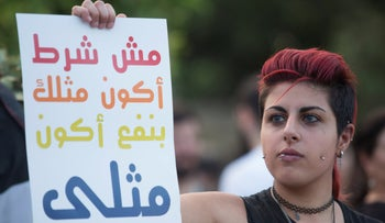 A protester holds a pro-LGBTQ rights sign at a protest in Haifa on August 1, 2019.