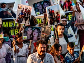 Yazidis march with pictures and banners during a demonstration in the Syrian town of Amude, August 3, 2018.