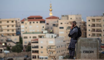 An Israeli police officer speaking on the phone with the East Jerusalem neighborhood of Isawiyah in the background, July 4, 2019.