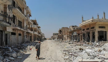 A man inspects the damages in the town of Khan Shaykhun in the southern countryside of Idlib, August 3, 2019.