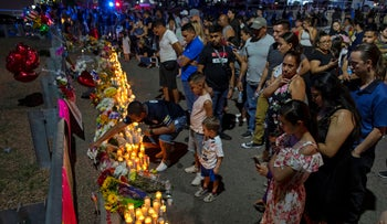 People gather at makeshift memorial for the victims of Saturday's mass shooting at a shopping complex in El Paso, Texas, August 4, 2019.