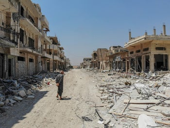 An aerial view taken on August 3, 2019, shows a Syrian man inspecting the damages in the town of Khan Sheikhun in the southern countryside of Idlib.
