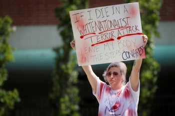 Mourner Amanda Luke holds a sign at vigil following a mass shooting in Dayton, Ohio, August 4, 2019.