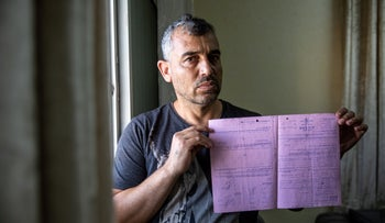 Samer Sleiman presenting the police search report in his Isawiyah home, August 5, 2019.