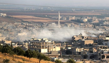 Smoke billowing above buildings during a reported air strike by pro-regime forces on Khan Sheikhun in the south of the northwestern Syrian province of Idlib, August 5, 2019.