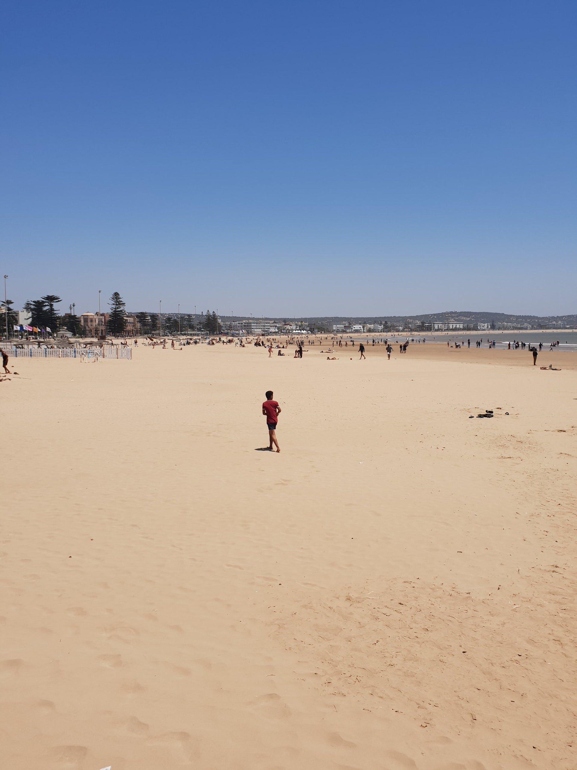 A kid is running on the beach in Essaouira.