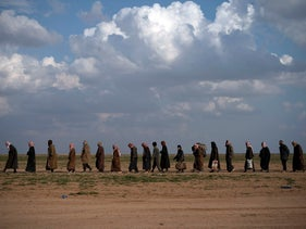 File photo: Men walk to be screened after being evacuated out of the last territory held by Islamic State militants, near Baghouz, eastern Syria, February 22, 2019.