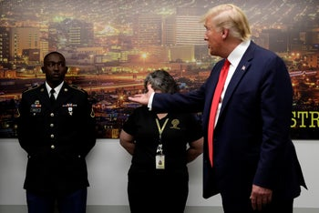 President Trump gestures to Army Pfc. Glendon Oakley, left, as he speaks to the media as he visits the El Paso Regional Communications Center, August 7, 2019.