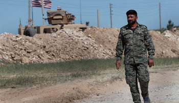 A U.S-backed Syrian Manbij Military Council soldier passes a U.S. position near the front line with Turkish-backed fighters, in Manbij, north Syria, April 4, 2018.