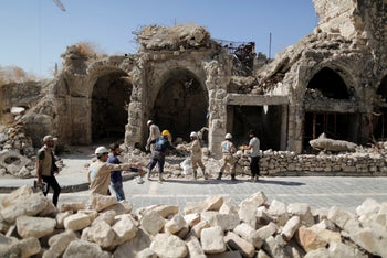Workers remove rubble from a damaged shop in the old city of Aleppo, Syria, on July 27, 2019.
