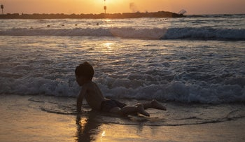 A Palestinian toddler plays on the beach in Tel Aviv for the first time.