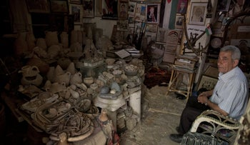 Walid al-Aqqad with Palestinian heritage pieces and antiques inside his private museum in Khan Yunis, July 14, 2019.