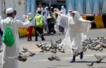 A Moroccan pilgrim runs as pigeons fly outside the Grand Mosque in the Muslim holy city of Mecca, Saudi Arabia, August 4, 2019.