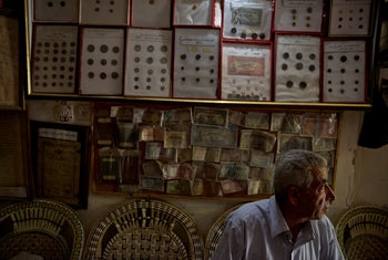 Walid al-Aqqad sits in front of old coins hanging on a wall inside Al-Aqqad private museum, July 14, 2019.