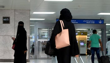 A Saudi woman rolls her suitcase at the departure hall of the Jeddah Airport on August 6, 2019.