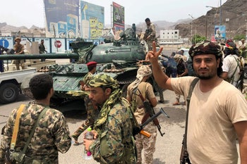 Yemeni supporters of the southern separatist movement pose for a picture with a tank they confiscated from a nearby military base in the southern Yemeni city of Aden on August 10, 2019.