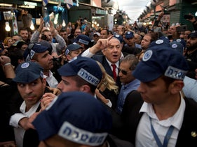 Israeli Prime Minister Benjamin Netanyahu, head of the Likud party, center, is escorted by security guards during a visit to the Hatikva market in Tel Aviv, Israel. April 2, 2019