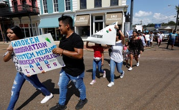 Children of mainly Latino immigrant parents hold signs in support of them and those individuals picked up during an immigration raid at a food processing plant in Canton, Miss., August 11, 2019.
