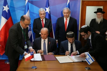 Prime Minister Benjamin Netanyahu looks on as Bezalel Smotrich signs an agreement during a visit by Chilean President Sebastián Piñera, June 26, 2019.