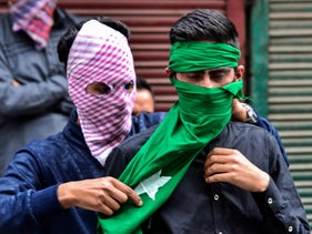 A Kashmiri protester helps a friend cover his face with a mask at a protest against Israel's occupation in Srinagar, Indian administered Kashmir, May 18, 2018