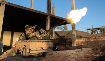A fighter from the former al-Qaeda Syrian affiliate Hayat Tahrir al-Sham (HTS) fires an anti-aircraft gun mounted on a pickup truck in Syria's southern Idlib province on August 7, 2019.