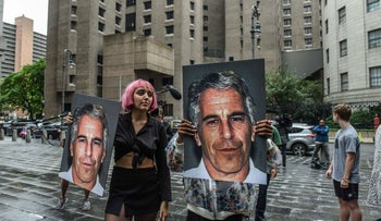 A protest group called 'Hot Mess' hold up signs of Jeffrey Epstein in front of the Metropolitan Correction Center in New York City, July 8, 2019.