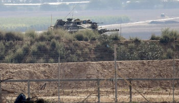 A picture taken from Khan Yunis shows an Israeli tank inspecting the area across the fence in the southern Gaza Strip, August 1, 2019.