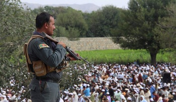 An Afghan policeman stands guard as Muslims listen during Eid al-Adha prayers in the Khost province, August 11, 2019.