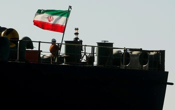 A crew member raises the Iranian flag at Iranian oil tanker Adrian Darya 1, previously Grace 1, in the Strait of Gibraltar, Spain, August 18, 2019.