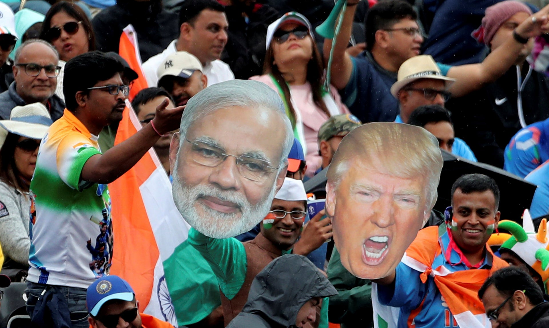Indian supporters display portraits of U.S. President Donald Trump and Indian Prime Minister Narendra Modi.