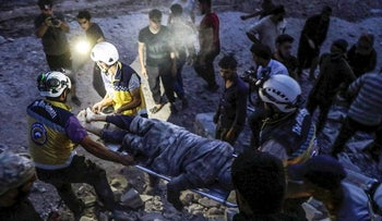"""Members of the Syrian Civil Defence, also known as the """"White Helmets"""", carry away on a stretcher a man rescued from the rubble of a collapsed building following a reported air strike in Kfar Ruma in Syria's northwestern Idlib province, on August 16, 2019"""